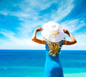 Woman in Blue Dress and Hat at Sea. Rear View. — Stok fotoğraf