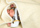 Baby boy is lying under blanket — Stock Photo