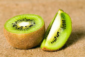 Green fruit kiwi on brown background — Stock Photo
