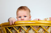 Boy is watching through a top of chair — Stock Photo