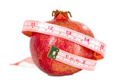 Tasteful fruit garnet with measuring tape — Stock Photo