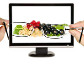 Man is viewing to currants with leaves on display — Stock Photo