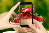 Man is taking photo of strawberries and jar — Stock Photo