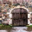 Stock Photo: Wooden door in stone wall