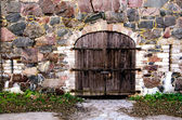 Wooden door in a stone wall — Stock Photo