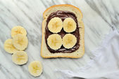 Bread with chocolate cream and slices of banana — Stock Photo