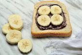 Bread with chocolate cream and sliced banana — Stock Photo