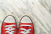 Used red sport shoes on marble background — Stockfoto