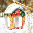 Snow covered colorful birdfeeder on the trunk of tree — Stock Photo
