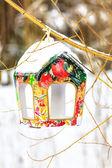 Comedero para pájaros colorido en el tronco del árbol nevado — Foto de Stock