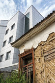 Ramshackle dilapidated abandoned old house and modern new building — 图库照片