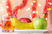 Banana, green and red apples on plate and glass of juice — Stock Photo