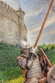 Armored knight on warhorse over old medieval castle — Stockfoto