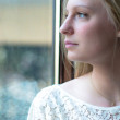 Woman standing by a window — Stock Photo #10858711