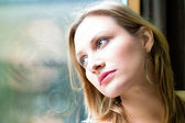 Woman standing by a window looking outside — Stock Photo