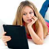 Woman on the couch with her tablet — Stockfoto