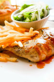 Chicken with sauce and golden French fries — Stock Photo