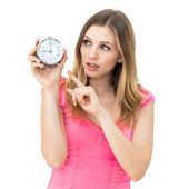 Aspetta, giovane bella donna tenendo un orologio — Foto Stock