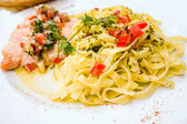 Plate of pasta and smoked salmon with tomato — Stock Photo