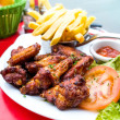 Chicken wings with sauce and golden French fries — Stok fotoğraf #49999913