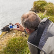 Photographer with digital camera - Latrabjarg Iceland — Стоковая фотография