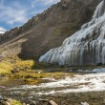 Young women on stone in background Dynjandi waterfall. — Stock Photo #18115127