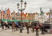 BRUGGE, BELGIUM - APRIL 22:Horses and carriages in the market pl — Stock Photo