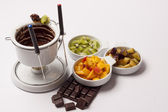 Chocolate fondue on white background — Stock Photo