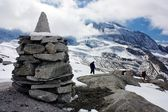 Stoneman with group of tourists and beautiful glacial mountains - mount Hochfeiler - Zillerttal Alps - Austria — Stock Photo