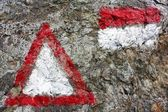 Red and white hiking trail signs symbols in Italy alps on grey background — Stock fotografie
