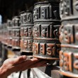 Stock Photo: Many prayer wheels and hand
