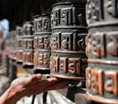 Many prayer wheels and hand — Stock Photo