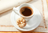 Cup of coffee on the white napkin — Stock Photo