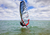 Man riding a windsurfing, huge bright sail, waves, strong wind, adrenaline — Stock Photo