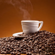 Cup of coffee and coffee beans on the background of Terracotta — Stock Photo