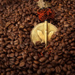 Spilled coffee beans and African medallion with eagle — Stock Photo