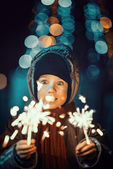 Portrait of a cute little boy holding sparklers — Stock Photo