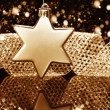 Christmas ball in star shape in front of a metal ribbon — Stock Photo