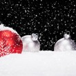 Foto Stock: Red and silver christmas balls in snow