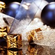 Tiny golden christmas present in front of christmas decoration — Stock Photo #12781150