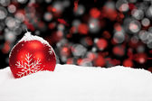 Red christmas ball in snow — Stock Photo