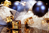 Tiny golden christmas present in front of christmas decoration — Stock Photo