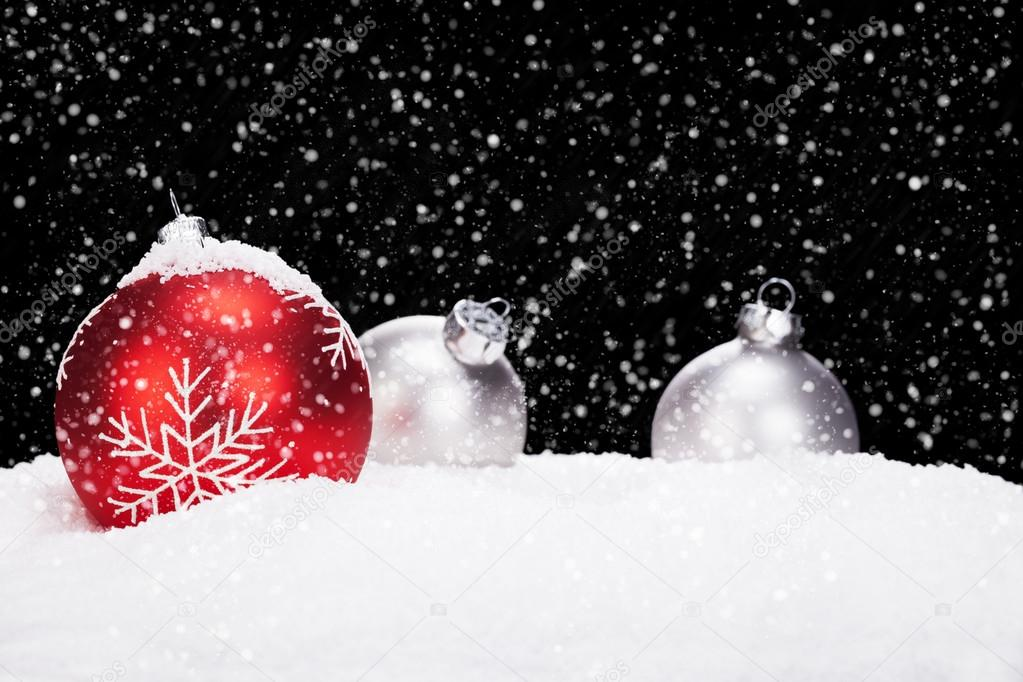 Red and silver christmas balls in snow on black background while snowing — Stock Photo #12781083