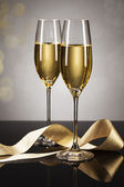Two glasses of champagne with a golden ribbon — Stock Photo