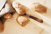 Broken rye bun with rye buns and a knife from top — Stock Photo