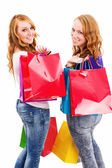 Two happy women with shopping bags turning around — Stock Photo