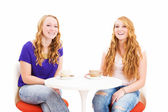 Two laughing redhead women sitting at a coffee table — Stock Photo