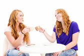 Two happy redhead women clink glasses with coffee cups — Stock Photo