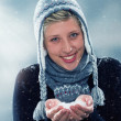 Young cute woman with a hand full of snow — Stock Photo