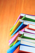 Colorful books isolated on wooden wall background — Stock Photo